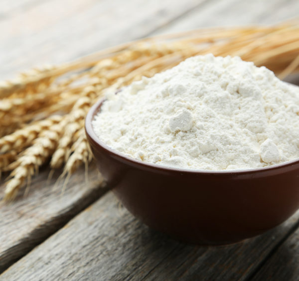 Bowl of wheat flour with spikelets on grey wooden background